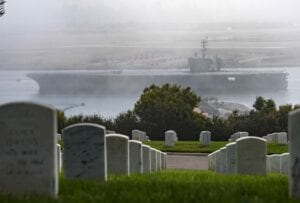 photo of US Navy ship in the background of an american military cemetery